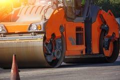 执行修理工作:涂柏油堆积和按沥青的热的位置路辗 修理路的机器 库存图片