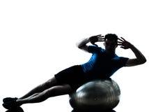 执行健身人姿势锻炼的球 免版税库存照片
