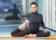 执行健身体操愉快的微笑的妇女 免版税库存图片