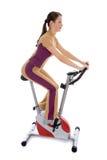 执行健身固定式妇女的自行车 免版税库存照片