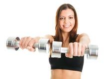 执行健身妇女的dumpbells 免版税库存照片