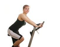 执行健身空转的妇女的自行车 免版税库存照片