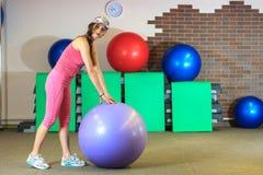执行健身他的人反映培训水 一套桃红色体育衣服的年轻美丽的白女孩做与紫罗兰色适合球的体育运动 库存照片
