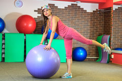 执行健身他的人反映培训水 一套桃红色体育衣服的年轻美丽的白女孩做与紫罗兰色适合球的体育运动 图库摄影
