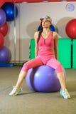 执行健身他的人反映培训水 一套桃红色体育衣服的年轻美丽的白女孩做与紫罗兰色适合球的体育运动 免版税库存照片