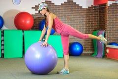 执行健身他的人反映培训水 一套桃红色体育衣服的年轻美丽的白女孩做与紫罗兰色适合球的体育运动 库存图片