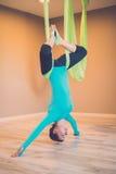 执行反地心引力的瑜伽的妇女 免版税库存照片