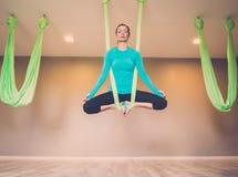 执行反地心引力的瑜伽的妇女 图库摄影