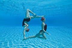 执行同步的游泳者在水面下 免版税库存图片