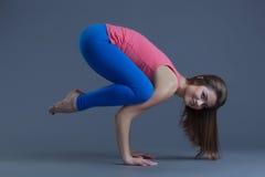 执行困难的瑜伽姿势的可爱的妇女 免版税图库摄影