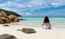 执行在一个热带海滩的妇女瑜伽 库存照片