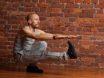 执行在一条腿的运动员人蹲坐 免版税库存照片