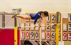 执行在单杠的年轻体操运动员女孩惯例 免版税库存照片