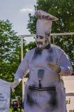 执行在厨师服装的艺术家 免版税库存照片