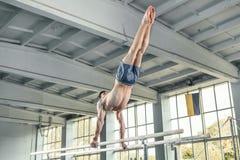 执行在双杠的男性体操运动员手倒立 免版税库存图片