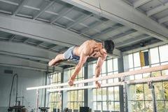 执行在双杠的男性体操运动员手倒立 免版税图库摄影