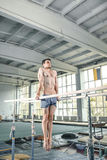 执行在双杠的男性体操运动员手倒立 图库摄影