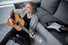 执行在吉他的无忧无虑的男性音乐家歌曲 免版税库存图片