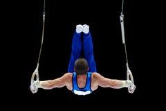 执行在圆环的体操运动员 免版税库存图片