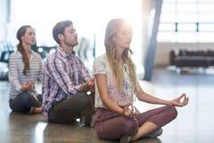 执行在地板上的商人瑜伽 免版税库存图片