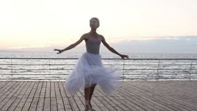 执行在堤防的年轻,美丽的跳芭蕾舞者竖趾旋转在海或海洋附近 白色长的芭蕾舞短裙的微笑的女孩 影视素材