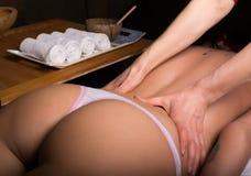执行在妇女身体的男按摩师按摩温泉沙龙的 轻松的妇女 秀丽处理概念 库存图片