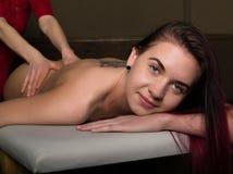 执行在妇女身体的男按摩师按摩温泉沙龙的 轻松的妇女 秀丽处理概念 库存照片