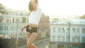 执行在屋顶的年轻女人有吸引力的跳舞-身分从地面-日落 股票视频