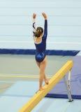 执行在平衡木的年轻体操运动员女孩惯例 免版税图库摄影