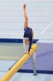 执行在平衡木的年轻体操运动员女孩惯例 库存图片