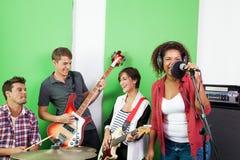 执行在录音室的乐队成员 图库摄影
