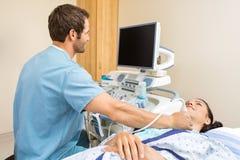 执行在患者的脖子的男性护士超声波 免版税库存照片