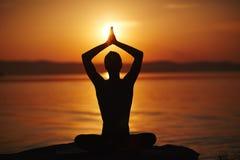 执行在日落的瑜伽 库存照片