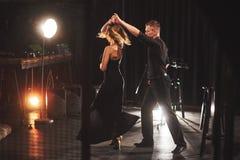 执行在暗室的纯熟舞蹈家在光下 库存图片
