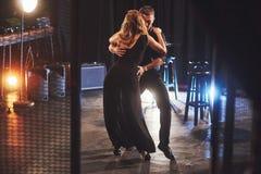 执行在暗室的纯熟舞蹈家在光下 免版税库存照片