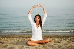 执行在海滩的俏丽的妇女瑜伽 库存图片