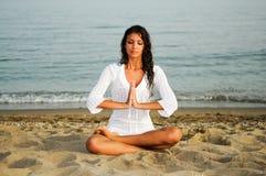 执行在海滩的俏丽的妇女瑜伽 免版税库存照片