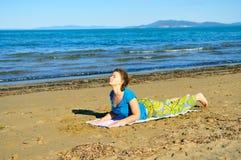 执行在海滩的好女孩瑜伽执行 免版税库存图片