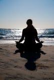 执行在海滩的妇女瑜伽。 免版税图库摄影