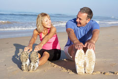 执行在海滩的高级夫妇 免版税图库摄影