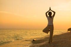 执行在海滩日落的女孩的剪影瑜伽 库存图片