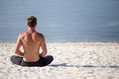执行在海滩的人瑜伽 免版税库存图片