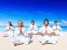 执行在海滩的人们瑜伽 免版税库存照片