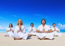 执行在海滩的人们瑜伽 库存照片
