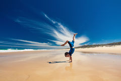 执行在海滩的杂技年轻男孩手立场 免版税图库摄影