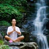 执行在瀑布女子瑜伽年轻人附近 免版税库存照片