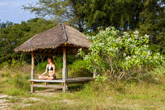 执行在热带眺望台的妇女瑜伽凝思 图库摄影