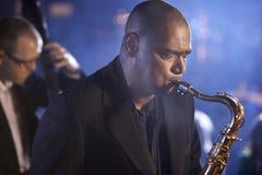 执行在爵士乐俱乐部的萨克斯管吹奏者和低音提琴球员 库存图片