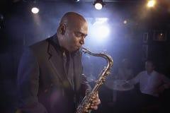 执行在爵士乐俱乐部的萨克斯管吹奏者 免版税库存图片