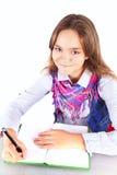 执行在白色的微笑的女孩家庭作业 库存照片